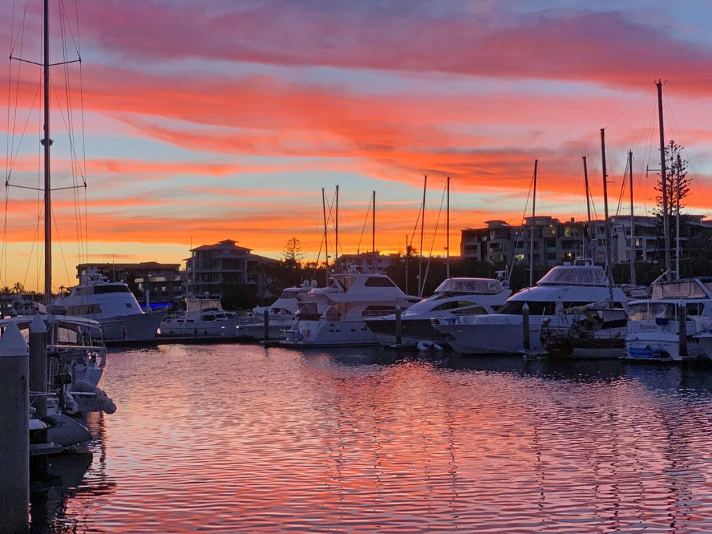 Orange and blue sunset over a marina with reflections in the water