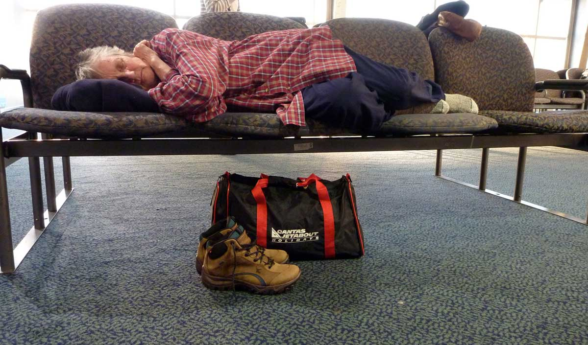 An older woman sleeping on a bench seat in an airport, her shoes and cabin bag on the floor beside her.